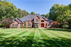 Luxury properties stately brick home on five wooded acres