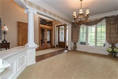 The dramatic two-story foyer is accented by hardwoods, faux finishes and a chandelier luxury homes
