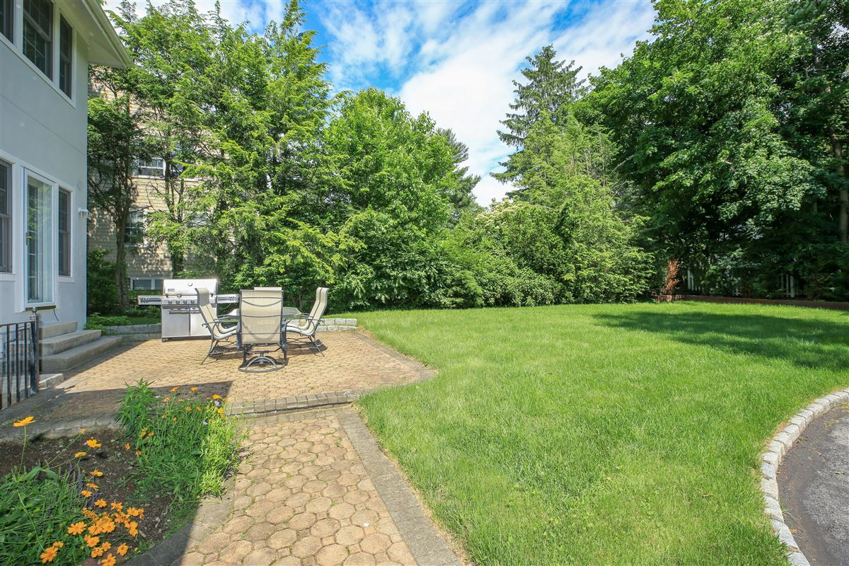 Luxury properties sunny Colonial on a tree-lined street