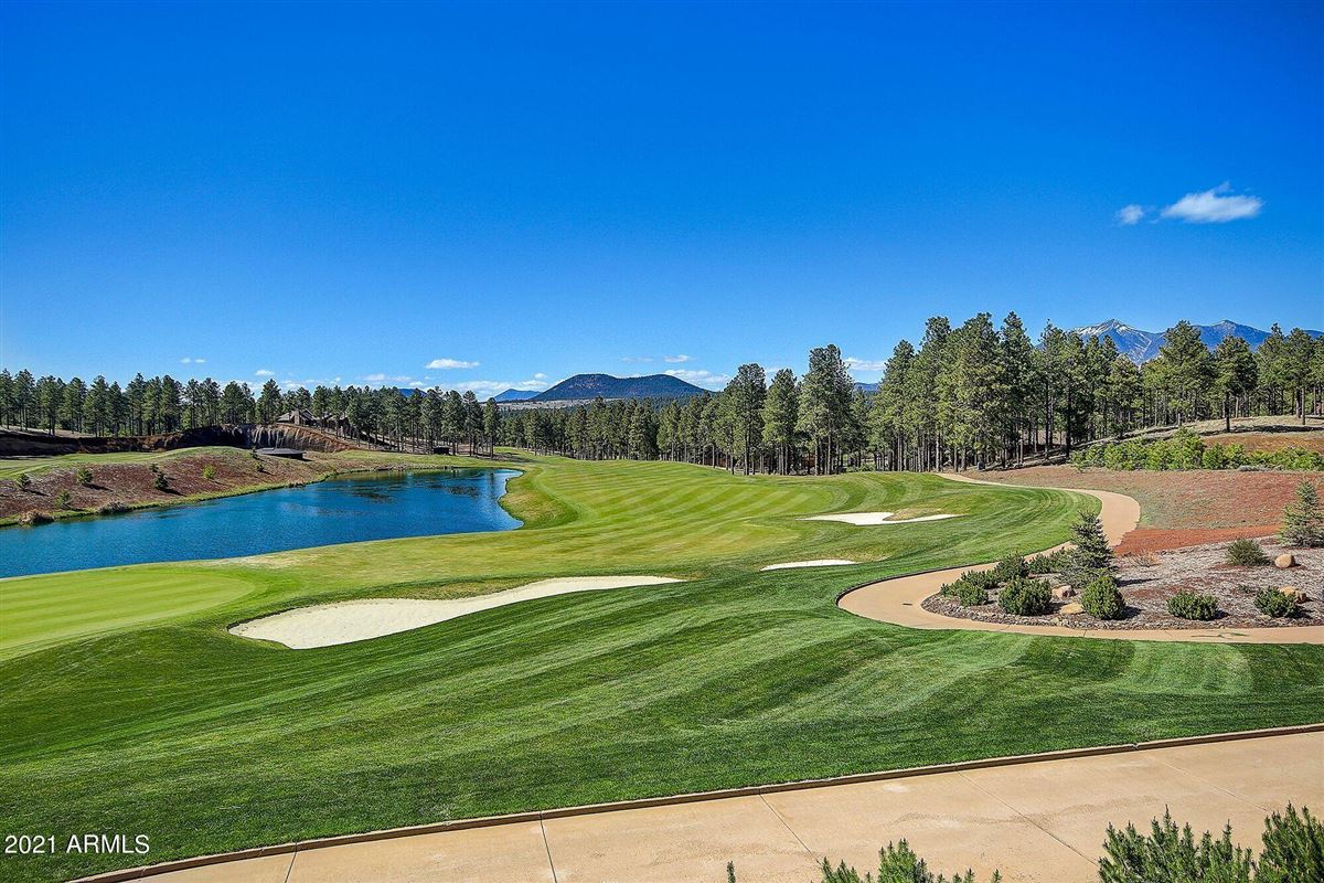 Luxury real estate beautiful home surrounded by lush landscaping creating privacy, mountain and golf course views